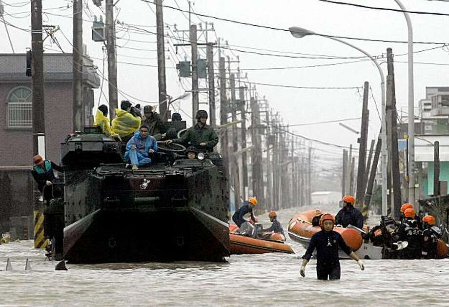 CORRECTING BYLINE Evacuees (L) sit on top of a military vehicle as rescuers (R) search the flooded area for people after rains brought by Typhoon Morakot inundated the area in Chiatung, Pingtung county, in southern Taiwan, on August 9, 2009.  One person was killed and eight were missing and feared dead in Taiwan as Typhoon Morakot lashed the island with powerful winds and downpours, rescuers said on August 8.    AFP PHOTO / PATRICK LIN (Photo credit should read PATRICK LIN/AFP/Getty Images) Photo: PATRICK LIN, AFP/Getty Images