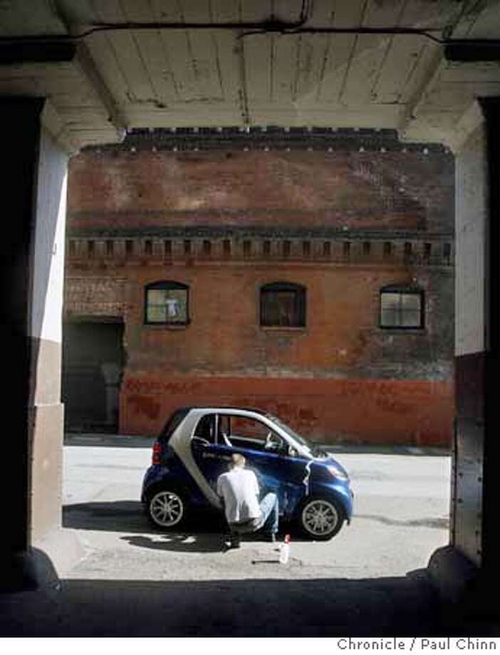 ###Live Caption:Shane Whiting applies decals to a tiny Smart Car in San Francisco, Calif., on Tuesday, March 18, 2008. When it goes into service the two-seater will be the first of its kind in City Car Share's Bay Area fleet but another one will be added soon. Photo by Paul Chinn / San Francisco Chronicle###Caption History:Shane Whiting applies decals to a tiny Smart Car in San Francisco, Calif., on Tuesday, March 18, 2008. When it goes into service the two-seater will be the first of its kind in City Car Share's Bay Area fleet but another one will be added soon. Photo by Paul Chinn / San Francisco Chronicle###Notes:Shane Whiting###Special Instructions:MANDATORY CREDIT FOR PHOTOGRAPHER AND S.F. CHRONICLE/NO SALES - MAGS OUT Photo: Paul Chinn