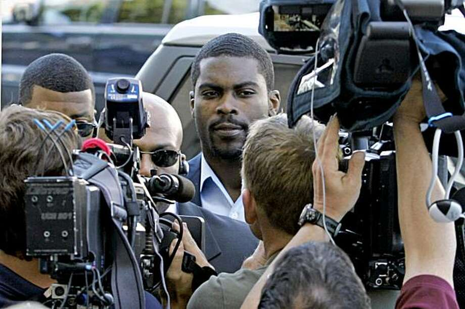 FILE - In this May 22, 2009, file photo, Michael Vick arrives at federal court surrounded by the media for a meeting with his parole officer in Norfolk, Va. Michael Vick's federal dogfighting sentence is scheduled to end Monday and that is also when he will go back on trial _ facing a whole new series of judgments.  NFL commissioner Roger Goodell, teams, fans and sponsors are among those who will weigh in on Vick's future.  (AP Photo/Steve Helber) Photo: Steve Helber, AP