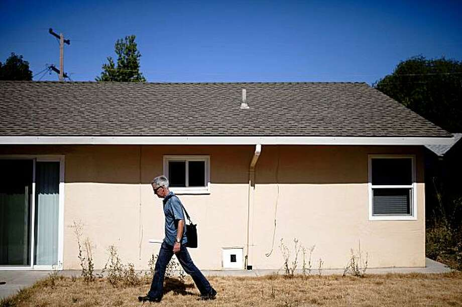 Working with Oakland's McKinley Partners, Paul Staley, vice president of Staley and MacArthur Inc Real Estate Services, surveys the backyard of a bank-owned house they're considering investing in Pittsburg, Calif. on Monday, July 27, 2009. McKinley has formed a $6 million fund to purchase foreclosed homes in eastern Contra Costa towns, forecasting their potentials to double its value in five years. Photo: Stephen Lam, The Chronicle