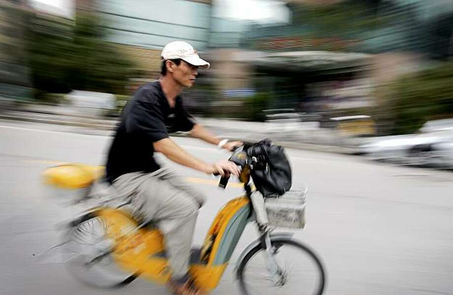 **ADVANCE FOR SUNDAY, JULY 26**In this photo taken Monday, June 29, 2009, a commuter ride electric bicycle in Shanghai, China.  Industry estimates put the number of electric bikes and scooters on the roads at more than 65 million. It's a trend catching on elsewhere, from remote Australian towns to chaotic New Delhi streets. (AP Photo) Photo: AP