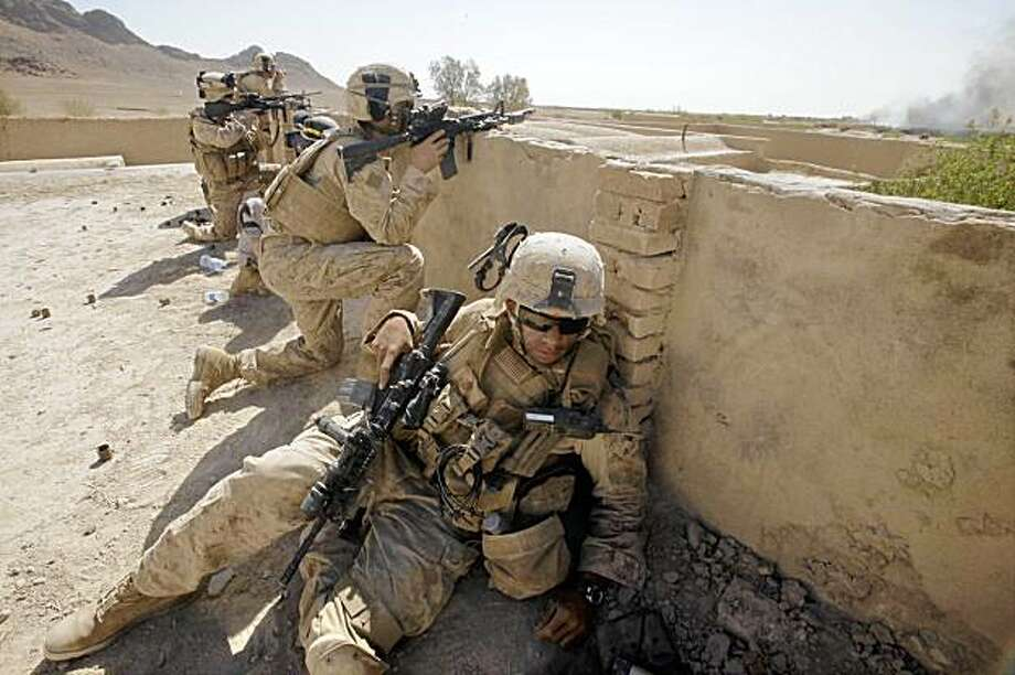 U.S. Marines of Golf Company, 2nd Battalion, 3rd Regiment take a position on a rooftop while fighting the Taliban in the village of Dahaneh Wednesday, Aug. 12, 2009, in the Helmand Province of Afghanistan. Operation Eastern Resolve 2 launched Wednesday morning in an attempt to push Taliban from the village which is a key commerce town in the province. (AP Photo/Julie Jacobson) Photo: Julie Jacobson, AP