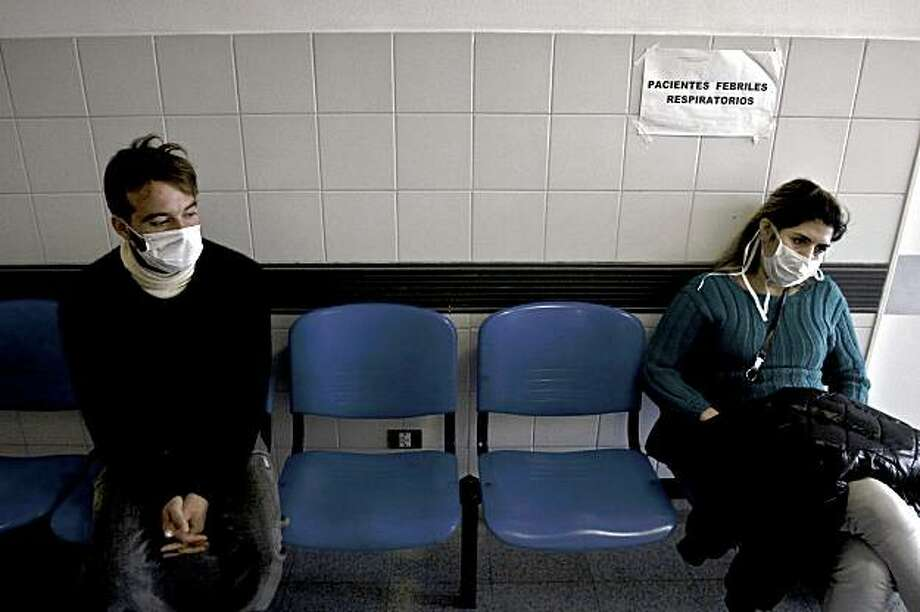 People wearing protective masks as a precaution against swine flu wait to be attended at a hospital in the outskirts of Buenos Aires, Wednesday, July 29, 2009. Argentina has the world's second-highest swine flu death toll after the U.S., but the virus is apparently still killing fewer people here than normal seasonal flu, good news for experts in the Northern Hemisphere who are watching closely to see how it evolves in the southern winter. (AP Photo/Pablo Barrera) Photo: Pablo Barrera, AP