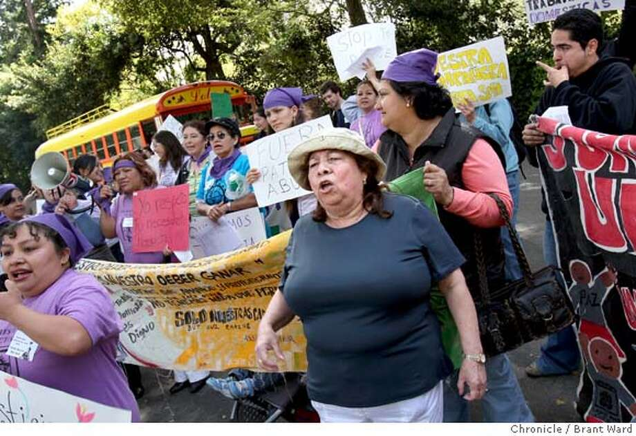Vilma Serralta, center in light hat, joined in the protest in front of her former employers house Thursday. Vilma Serralta is suing her former employers in Atherton, CA because she says she was overworked and underpaid as a live-in . Photo by Brant Ward / San Francisco Chronicle Photo: Brant Ward