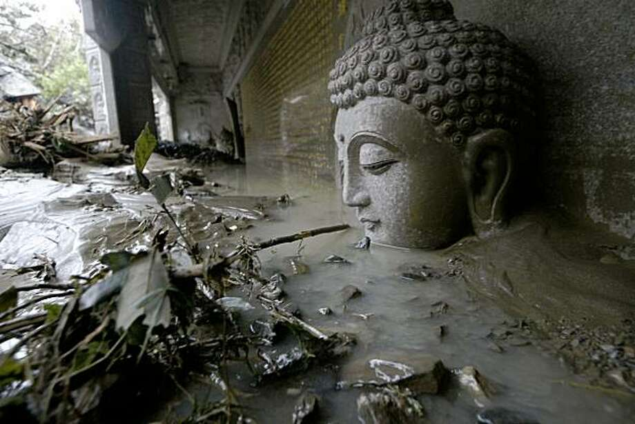 A statue of Buddha's head is seen submerged in flood water and debris from Typhoon Morakot at a temple in Kaohsiung County, southern Taiwan Tuesday, Aug. 11, 2009. Rescue officials have said more than 300 people were ferried from disaster areas on more than 100 emergency flights. (AP Photo) Taiwan Out Photo: AP