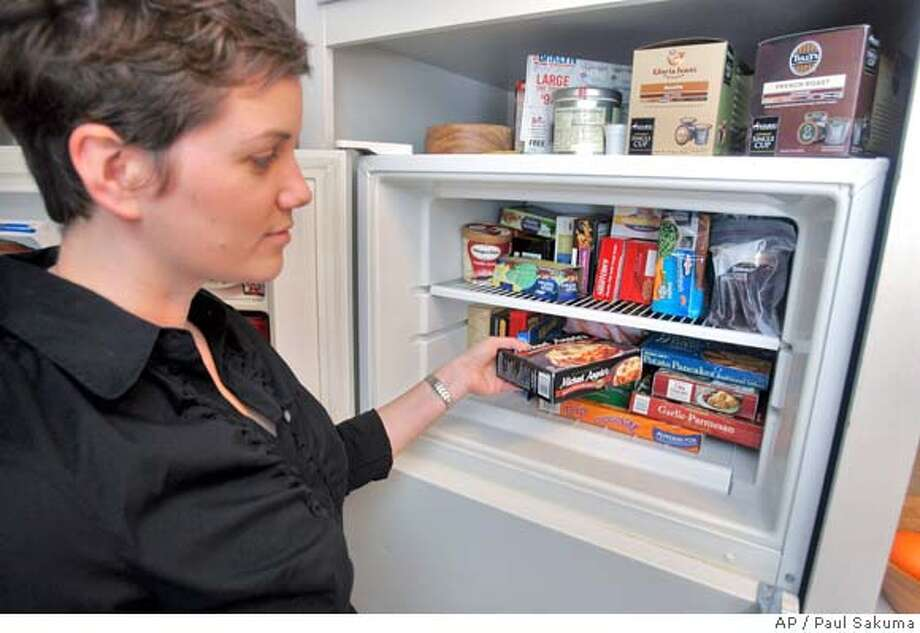 Abi Jones, of HeatEatReview.com, pulls out a frozen food item for dinner and review from her freezer in Palo Alto, Calif., Wednesday, March 5, 2008. Obsessive Web sites evaluating the newest eats have become must-reads for lovers of every type of food including frozen dinners, potato chips, candy bars and even energy drinks. (AP Photo/Paul Sakuma) Photo: Paul Sakuma