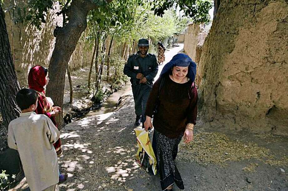 Sima Matin, right, a female candidate in a provincial council election, walks on her way to take part in a campaign with her security guard  in Shirak Pirak in Kapisa province, north of Kabul, Afghanistan on Tuesday July 28, 2009.  For women running for office in one of the world's most conservative countries, getting out the vote is an uphill battle against social norms. In a place where most women still wear the burqa and do not speak to men outside their immediate family, female candidates are pushing the envelope simply by putting up posters of their uncovered faces. They risk being called prostitutes for trying to explain their platforms to male voters. (AP Photo/Rafiq Maqbool) Photo: Rafiq Maqbool, AP