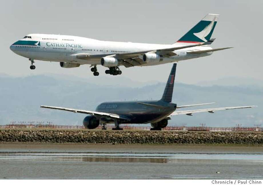 A Cathay Pacific jumbo jet comes in for a landing above a United jet waiting to take off at San Francisco International Airport on Wednesday, March 26, 2008. Airport officials are considering raising fees for flights landing at peak times and lowering rates for off-peak arrivals.  Photo by Paul Chinn / San Francisco Chronicle Photo: Paul Chinn