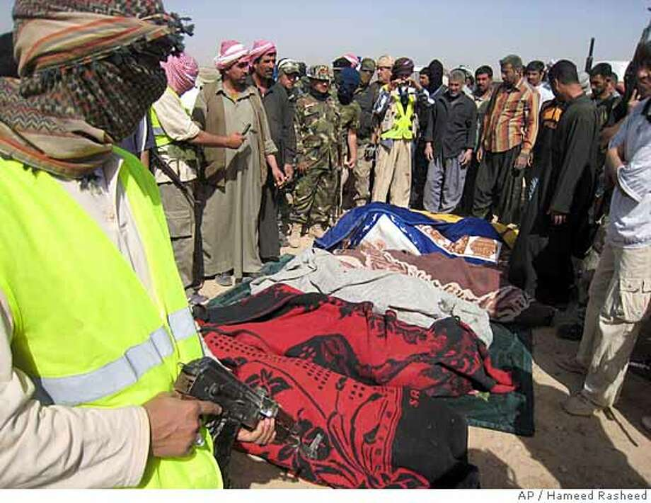 Awakening council members, a Sunni group fighting al-Qaida, stand around the bodies of six of their comrades killed in a U.S. air strike near Samarra, Iraq, Saturday, March 22, 2008. Police say a U.S. airstrike has struck checkpoints manned by U.S.-allied Sunni fighters north of Baghdad, killing six guards and wounding two. A police officer says the six members of the so-called awakening council were killed and two others were wounded when an airstrike hit two checkpoints about 100 meters (yards) apart. A local awakening council leader says the airstrikes came some two hours after U.S. soldiers stopped at the two checkpoints to meet with the Sunni fighters. (AP Photo/Hameed Rasheed) Photo: HAMEED RASHEED