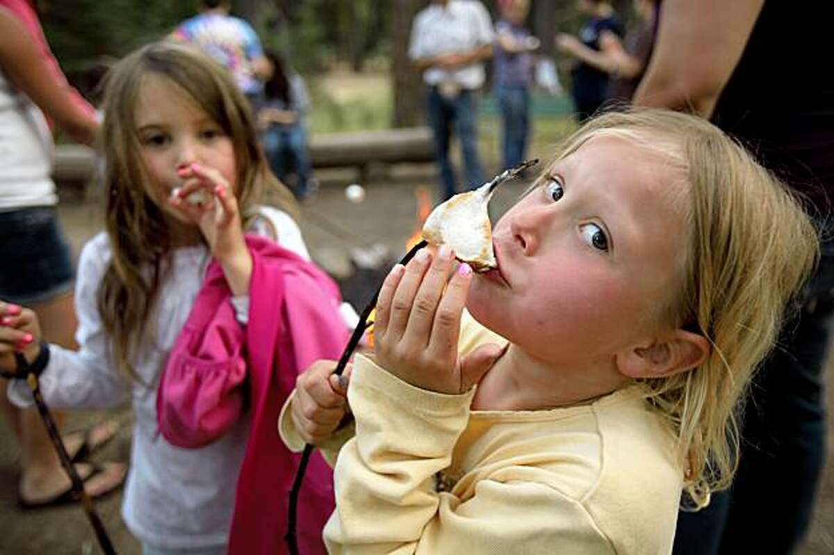Sophia Compton and Grace Sandbatch enjoy roasted marshmallows during a hayride excursion at Camp Mather on Wednesday, July 30, 2009. Mather Saddle and Pack Station owner, Jay Barnes says he's seen a downturn in ride participants because of the economic slump. Camp Mather, which until now has always been booked solid and is the coveted summer prize for families year after year, has seen a dip in attendance from a downturn in the economy. Mather is a San Francisco institution. It is a tradition for many, many families and is one of the few affordable getaways for city kids and middle class families.