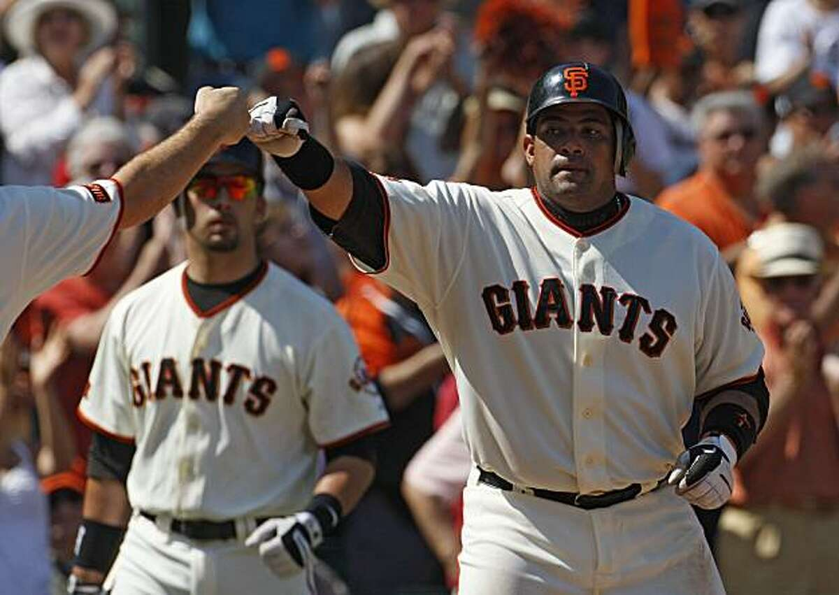 Giants Bengie Molina receives high-five's from his teammates after hitting a home run off the Cincinnati Reds in the 8th inning at AT&T Park in San Francisco, Calif., on August 8, 2009.