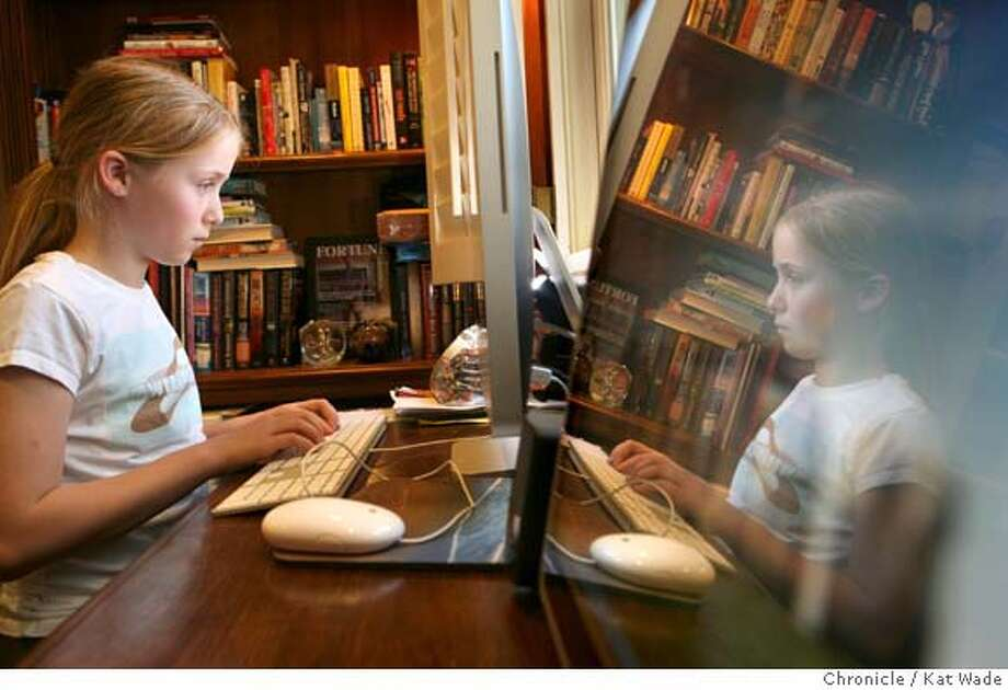 Ten-year-old Danielle DeCesare uses the internet to write a report on Mission Santa Barbara on a mac while reflected in a PC that her brother uses to play internet games at home in Blackhawk, Calif. on Thursday, March 13, 2008.  Photo by Kat Wade / Special to the Chronicle Photo: Kat Wade