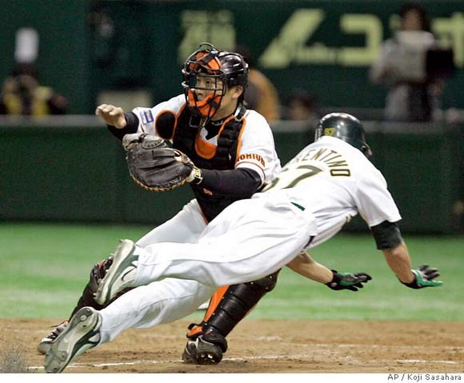 Oakland Athletics outfielder Jeff Fiolentino dives to home scoring on Rob Bowen's double past Yomiuri Giants catcher Ken Kato in the ninth inning of their exhibition baseball game at Tokyo Dome in Tokyo, Saturday, March 22, 2008. The Athletics won 4-3. (AP Photo/Koji Sasahara) Photo: Koji Sasahara