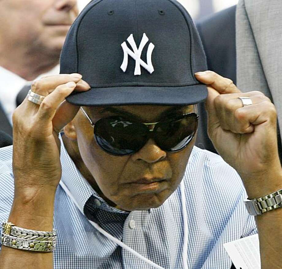 Muhammad Ali adjusts a New York Yankees cap given to him by Yankees shortstop Derek Jeter before the Red Sox faced the Yankees in a baseball game at Yankee Stadium in New York, Thursday, Aug. 6, 2009. (AP Photo/Kathy Willens) Photo: Kathy Willens, AP