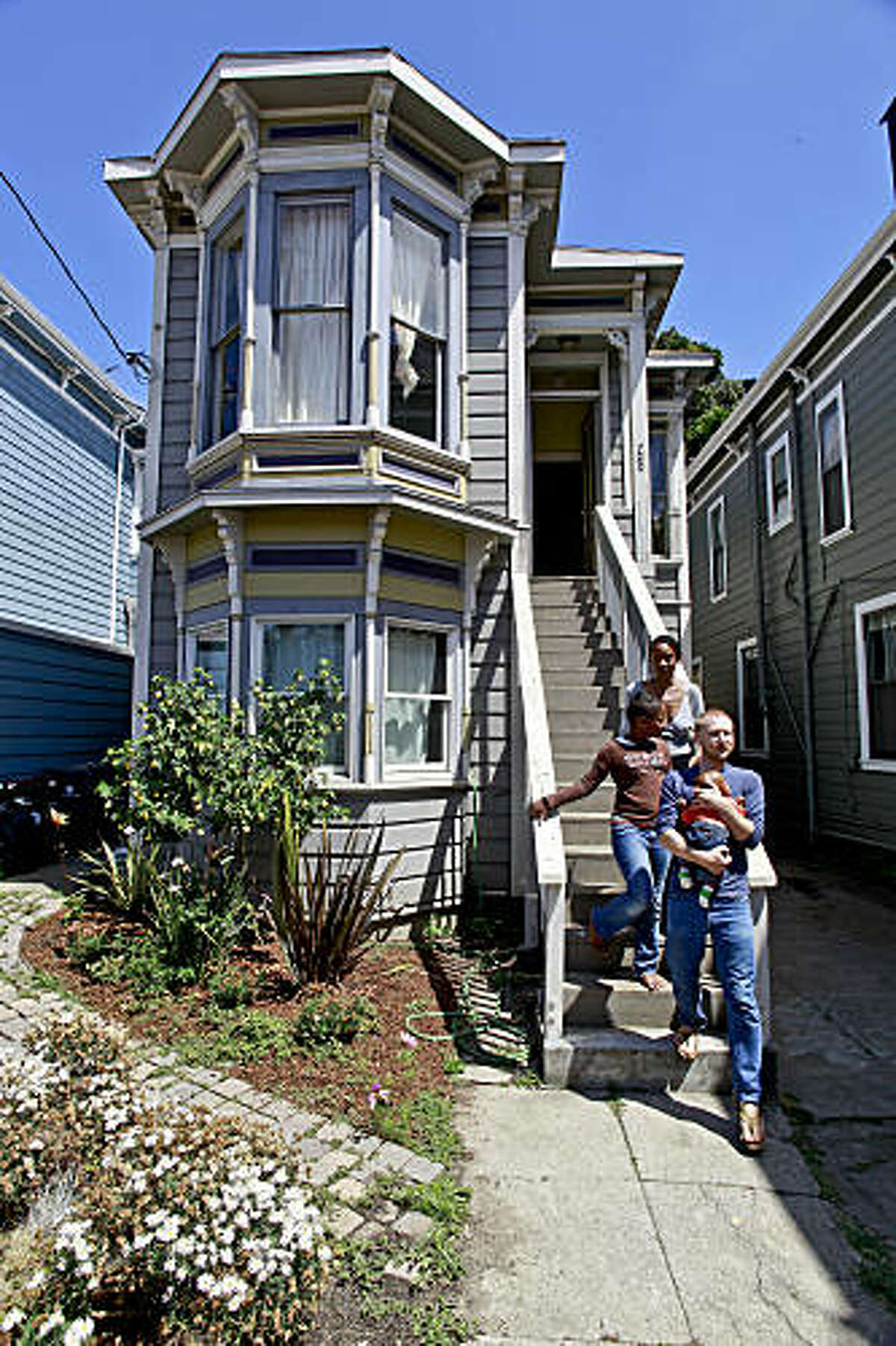 Andrei Soroker, on Wednesday July 22, 2009,at his home in Oakland, Calif. which he purchased two years ago with a present day mortgage of $500,000 and the value less than half of that. Soroker with his son Boris, 7-months-old, wife Ayana and daughter Harmony, 9-years-old. Soroker came up with a creative solution, creating a web site where he performs songs in English and Russian and invites visitors to contribute money towards his home.