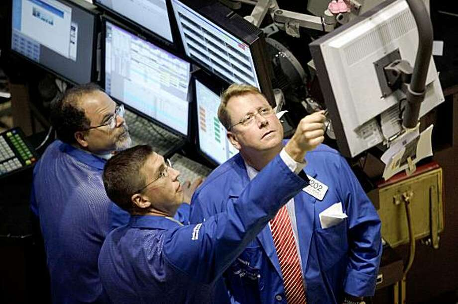 Traders work on the floor of the New York Stock Exchange Thursday, July 23, 2009 in New York. Investors celebrated news of another jump in home sales by propelling the Dow Jones industrials to their first close above 9,000 since January. (AP Photo/Mary Altaffer) Photo: Mary Altaffer, AP