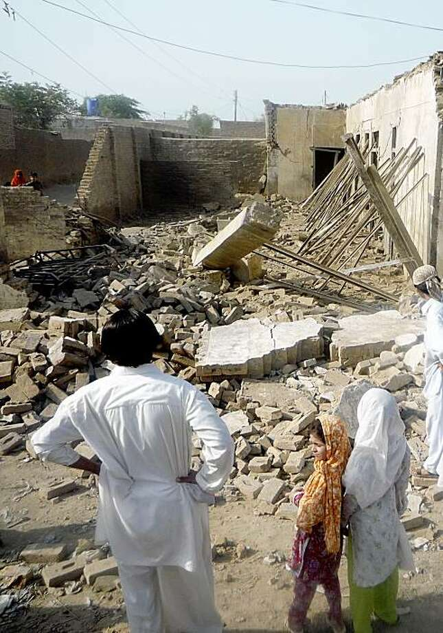 In this photo taken Tuesday, Aug. 4, 2009, Pakistani villagers look at a house belonging to supporters of Pakistani Taliban leader Baitullah Mehsud which was destroyed by authorities in Dera Ismail Khan, Pakistan.  (AP Photo/Ishtiaq Mehsud) Photo: Ishtiaq Mehsud, AP