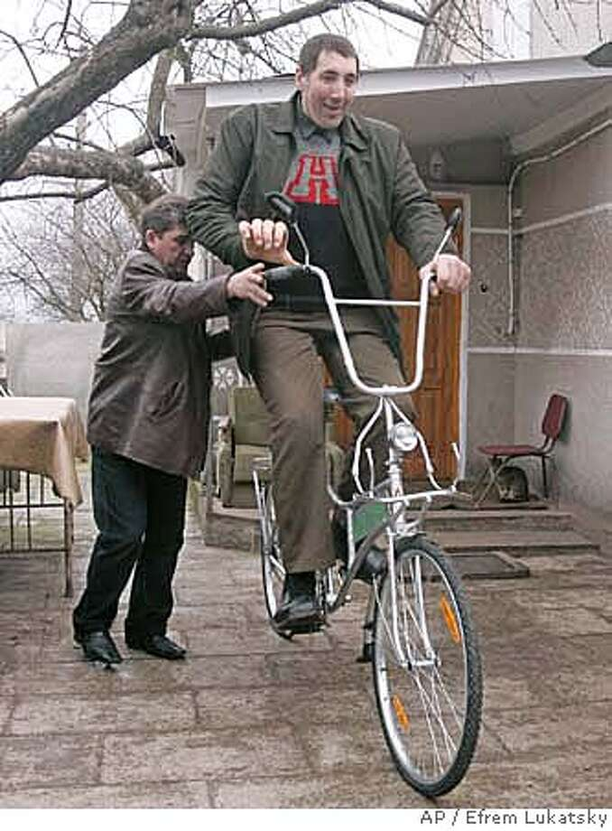 ###Live Caption:Ukrainian veterinarian, Leonid Stadnik, 2.59 meter (8,5 feet) tall, the world's tallest living man according to the Guinness Book of Records, rides a bicycle specially made for him, in the village of Podoliantsy, Ukraine's northwestern Zhytomyr region, 212 kilometers (131.74 miles) west of the capital Kiev, Sunday, March 23, 2008. Stadnik's growth spurt started at age 14 after a brain operation apparently stimulated his pituitary gland. Stadnik, 37, is still growing up. (AP Photo/Efrem Lukatsky)###Caption History:Ukrainian veterinarian, Leonid Stadnik, 2.59 meter (8,5 feet) tall, the world's tallest living man according to the Guinness Book of Records, rides a bicycle specially made for him, in the village of Podoliantsy, Ukraine's northwestern Zhytomyr region, 212 kilometers (131.74 miles) west of the capital Kiev, Sunday, March 23, 2008. Stadnik's growth spurt started at age 14 after a brain operation apparently stimulated his pituitary gland. Stadnik, 37, is still growing up. (AP Photo/Efrem Lukatsky)###Notes:###Special Instructions: Photo: EFREM LUKATSKY