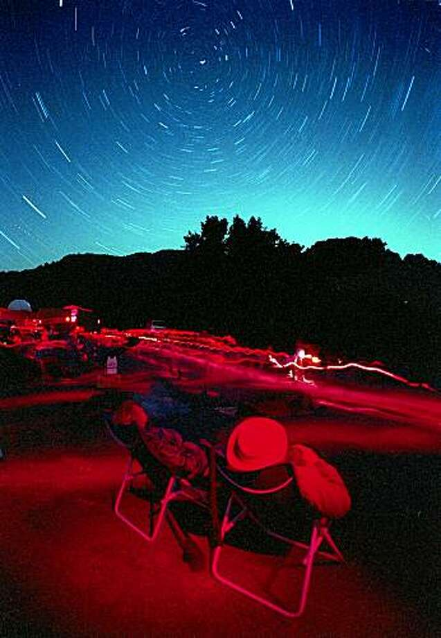PERSEID-C-12AUG02-MT-JLT   Dickson Yeager and wife B. J. Yeager (cq, right) of Santa Rosa joined hundreds of skywatchers watching the annual Perseid meteor shower at Robert Ferguson Observatory (extreme left)  in Sugarloaf Ridge State Park above Kenwood, CA.  (Circular streaks in sky are star trails centered on Polaris, caused by long exposure.  Streaks on ground are caused by folks with their red-filtered flashlights.) CHRONICLE STAFF PHOTO BY JERRY TELFER PERSEID-C-12AUG02-MT-JLT Dickson Yeager and wife B. J. Yeager (cq, right) of Santa Rosa joined hundreds of skywatchers watching the annual Perseid meteor shower at Robert Ferguson Observatory (extreme left) in Sugarloaf Ridge State Park above Kenwood, CA. (Circular streaks in sky are star trails centered on Polaris, caused by long exposure. Streaks on ground are caused by folks with their red-filtered flashlights.)  CHRONICLE STAFF PHOTO BY JERRY TELFER Photo: Jerry Telfer, The Chronicle