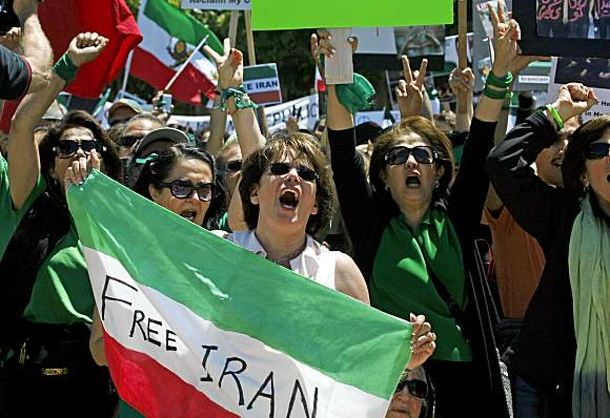Bahare Shabani from Houston Texas holds the Iranian flag as she joined several thousand who took part in a