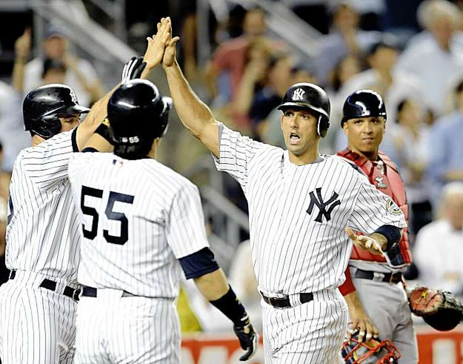 NEW YORK - AUGUST 6:  Jorge Posada #20 of the New York Yankees high fives his teammates at home plate after hitting a three run home run in the fourth inning as catcher Victor Martinez # 41 of the Boston Red Sox watches on August 6, 2009 at Yankee Stadium in the Bronx borough of New York City.  (Photo by Paul Bereswill/Getty images) Photo: Paul Bereswill, Getty Images