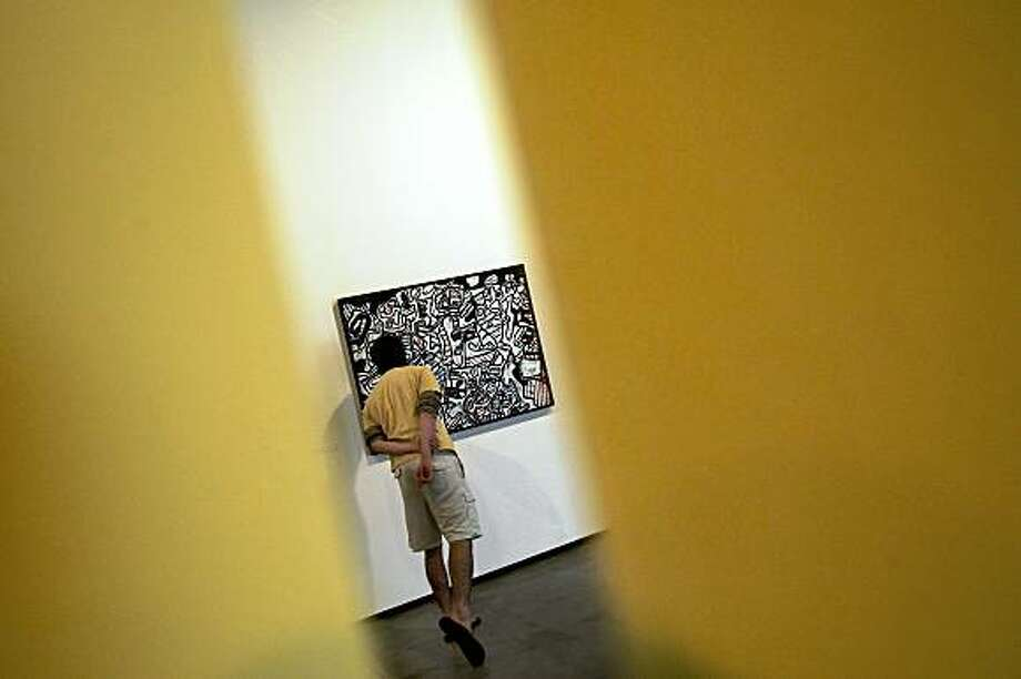 "A visitor looks at the painting ""Jardin l'Hourloupe-1966"" during the opening day of French artist Jean Dubuffet (1901-1985) restrospective exhibition, as part of Year of France in Brazil celebrations, in Sao Paulo, Brazil, on July 16, 2009. Dubuffet's retrospective, for the first time in Latin America, runs until September 7. Photo: Mauricio Lima, AFP/Getty Images"