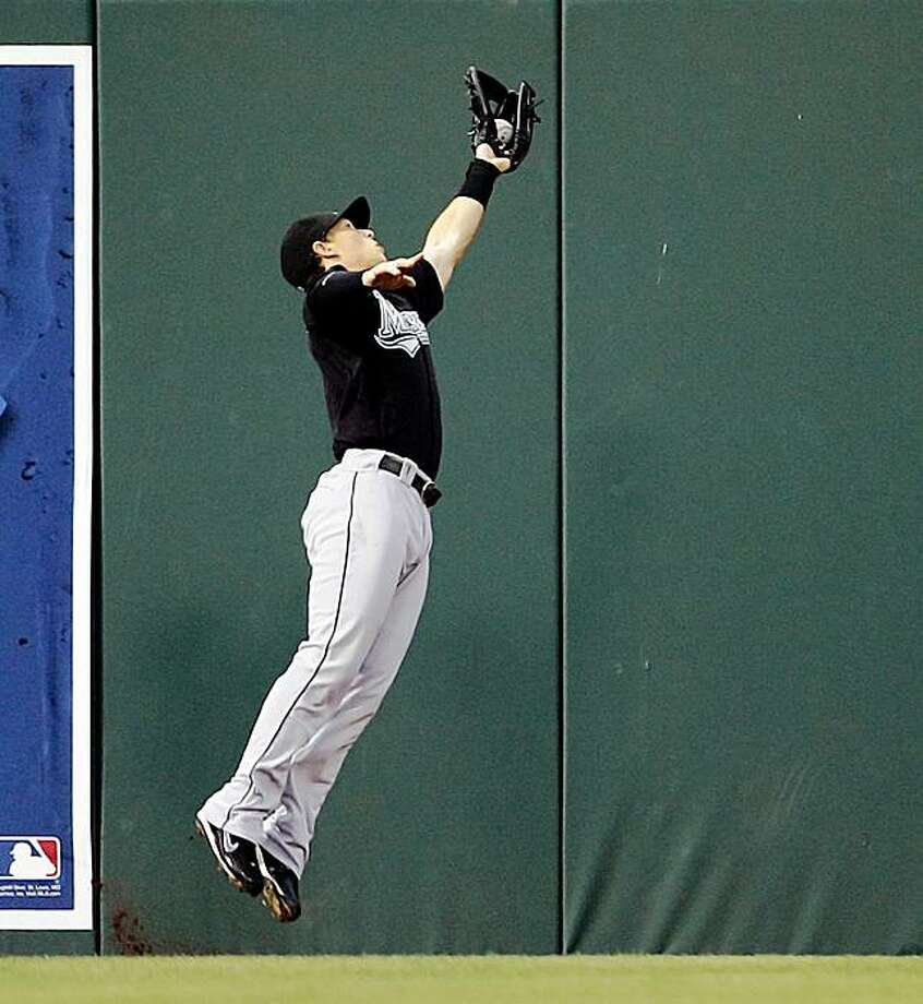 Florida Marlins' left fielder Chris Coghlan leaps to catch the fly ball hit by Philadelphia Phillies' Pedro Feliz in the second inning of a baseball game Saturday, Aug. 8, 2009, in Philadelphia.(AP Photo/Tom Mihalek) Photo: Tom Mihalek, AP