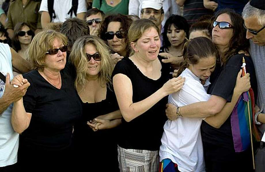 Relatives of Israeli Nir Katz, who was killed in an attack on a gay club, grieve during his funeral in the Israeli city of Modiin near Tel Aviv on August 2, 2009. Katz was killed on August 1 when a man opened fire in a gay youth club in Tel Aviv, killing him and a teenage girl, in an attack that struck fear among the liberal city's homosexual community. Israeli police have launched a manhunt for the assailant. AFP PHOTO/DAVID FURST (Photo credit should read DAVID FURST/AFP/Getty Images) Photo: David Furst, AFP/Getty Images