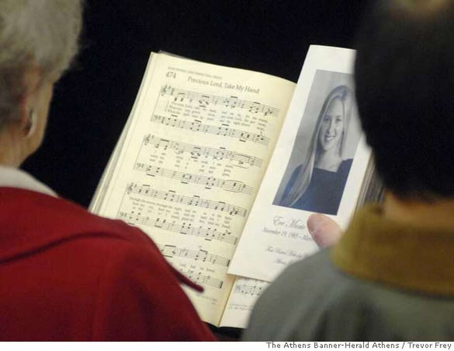 ###Live Caption:A woman holds the funeral program showing a picture of Eve Marie Carson, 22, during the service at First United Methodist church in Athens, Ga. on Sunday, March 9, 2008. Carson, a native of Athens, Ga., was murdered on March 5 in Chapel Hill, N.C., were she attended the University of North Carolina. Police said she was likely was the victim of a random crime. (AP Photo/The Athens Banner-Herald Athens, Trevor Frey)###Caption History:A woman holds the funeral program showing a picture of Eve Marie Carson, 22, during the service at First United Methodist church in Athens, Ga. on Sunday, March 9, 2008. Carson, a native of Athens, Ga., was murdered on March 5 in Chapel Hill, N.C., were she attended the University of North Carolina. Police said she was likely was the victim of a random crime. (AP Photo/The Athens Banner-Herald Athens, Trevor Frey)###Notes:###Special Instructions:MANDATORY CREDIT Photo: Trevor Frey