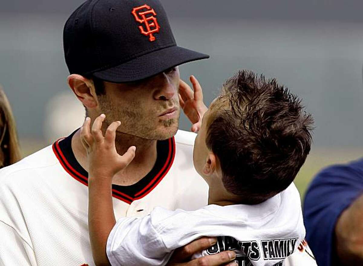 Giants Freddy Sanchez gets a hug from his son 'Even age 4 during the Giants family solfball game prior to the start of the Giants Philadelphia Phillies game Saturday night August 1, 2009