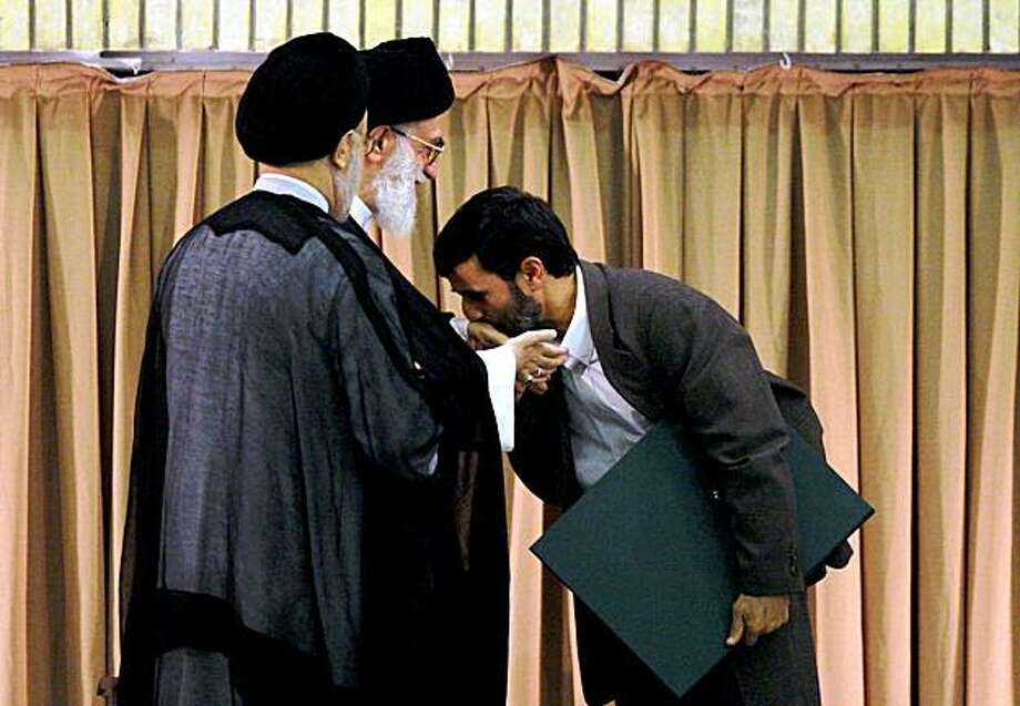 FILE  -- In this Wednesday Aug. 3, 2005 file photo Iran's new President Mahmoud Ahmadinejad, right, kisses the hand of Iran's supreme leader Ayatollah Ali Khamenei's,  as former President Mohammad Khatami, left, looks on during  Ahmadinejad's inaugural ceremony in Tehran four years ago. Iran's supreme leader formally endorsed Mahmoud Ahmadinejad for second term as president Monday, Aug. 3, 2009, in a ceremony that sought to portray unity among the country's leadership but was snubbed by prominent critics of the disputed election. After Ayatollah Ali Khamenei gave his official seal of approval, he allowed Ahmadinejad to kiss his robe on his shoulder _ a noticeably more restrained gesture than four years ago when Ahmadinejad kissed the leader's hand and cheeks in a sign of closeness and loyalty.  (AP Photo/Hasan Sarbakhshian/file) Photo: Hasan Sarbakhshian, AP