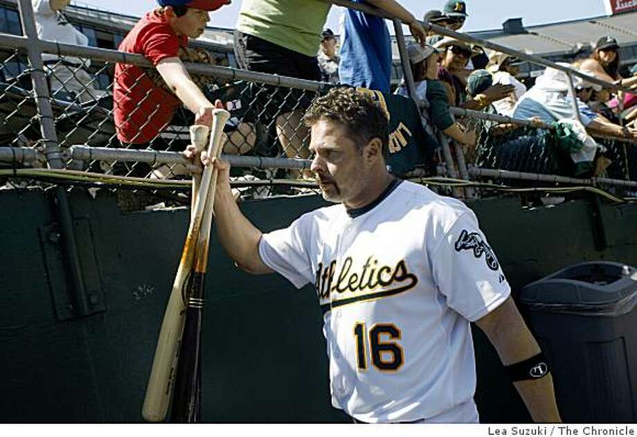 Jason Giambi raises a handful of bats to high five a fan as he leaves the field after the Oakland Athletics defeated the Baltimore Orioles in Oakland on Sunday. Photo: Lea Suzuki, The Chronicle