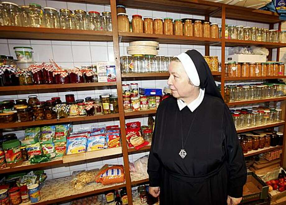 **ADVANCE FOR SUNDAY, JULY 19** In this June 23, 2009 photo,  Sister Anastazja Pustelnik shows visitors her panty stocked with food in Krakow, Poland. The Polish nun has published five cookbooks that have sold more than 1.1 million copies, making her one of the top-selling cookbook authors in the mainly Roman Catholic country.  ( AP Photo/Czarek Sokolowski) Photo: Czarek Sokolowski, AP