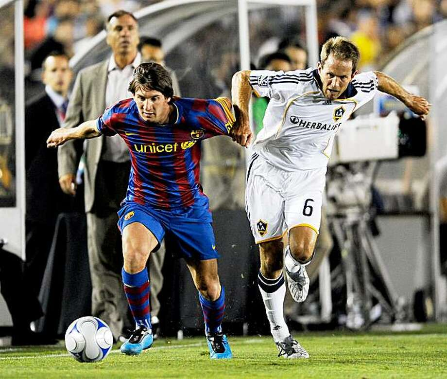 PASADENA, CA - AUGUST 01:  Lionel Messi #10 of FC Barcelona has his shirt pulled by Eddie Lewis #6 of the Los Angeles Galaxy during the first half of the friendly soccer match at the Rose Bowl on August 1, 2009 in Pasadena, California.  (Photo by Kevork Djansezian/Getty Images) Photo: Kevork Djansezian, Getty Images