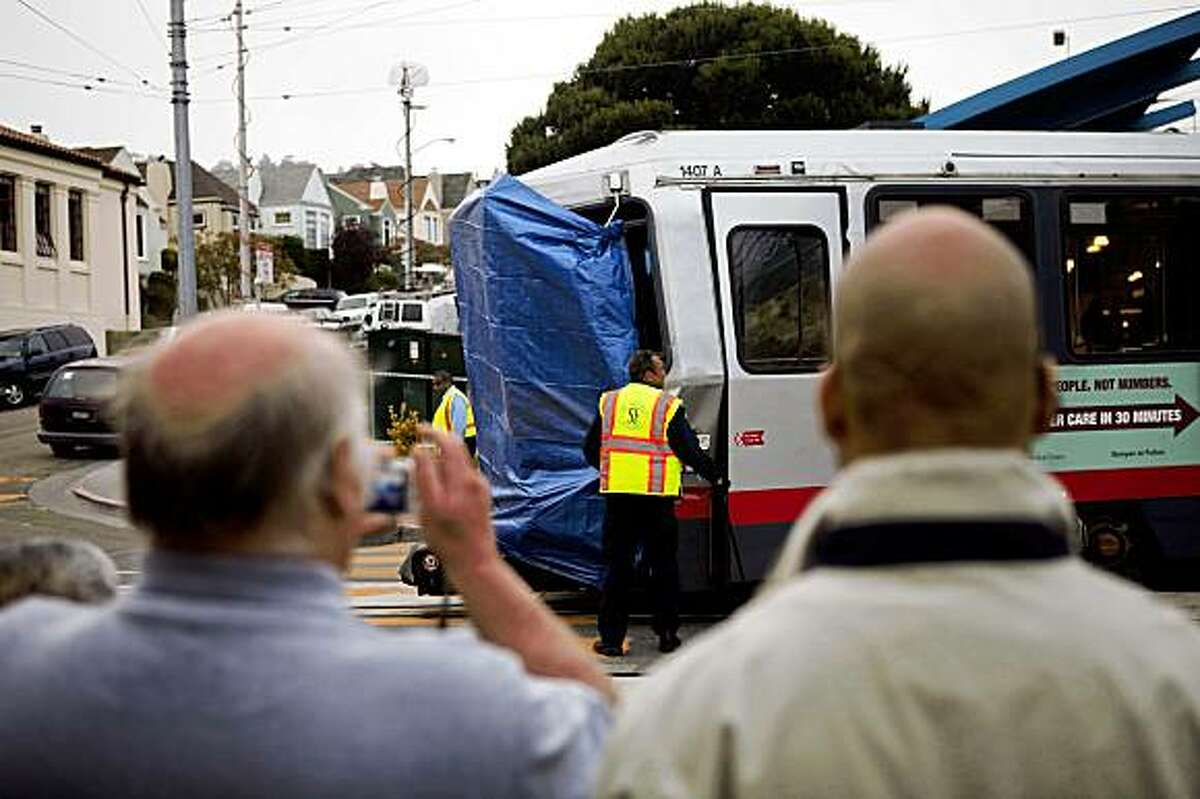 Onlookers watch as a damaged Muni train is moved under the guidance of MUNI personnel after a collision between an outbound L Taraval and K Ingleside train at the West Portal Station in San Francisco, Calif. Saturday, July 18, 2009.