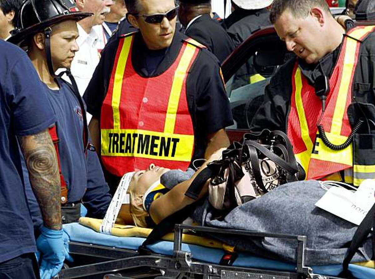 San Francisco Firefighters talk with one of the victims involved in a two train Muni crash at the West Portal Station on Saturday, July 18, 2009.
