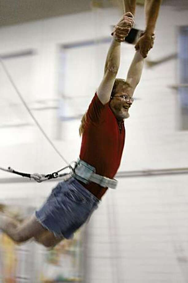 Donald Robertson, 52, is caught in mid-air while swinging from a trapeze at Circus Center in San Francisco, Calif., on June 25, 2009. Photo: Frederic Larson, The Chronicle