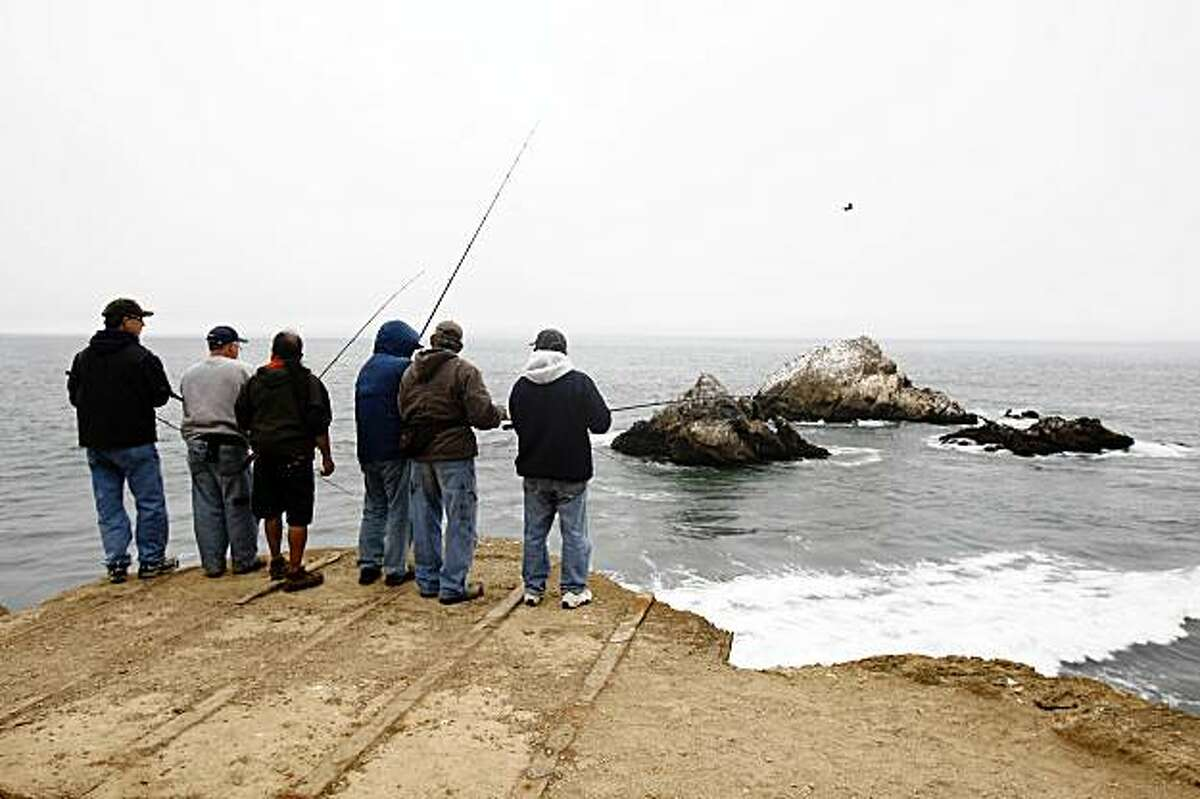 A group of people fish behind the Cliff House with Seal Rocks in the background on Wednesday July 29, 2009 in San Francisco, Calif.