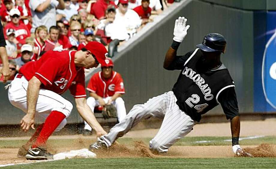 Colorado Rockies' Dexter Fowler, right, slides safely into third base for a triple ahead of the tag from Cincinnati Reds third baseman Adam Rosales, left, in the 11th inning during a baseball game, Sunday, Aug. 2, 2009, in Cincinnati. The Rockies won 6-4. (AP Photo/David Kohl) Photo: David Kohl, AP