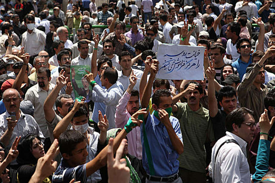 """Iranian opposition supporters protest in Tehran after powerful cleric Akbar Hashemi Rafsanjani ended his Friday prayers sermon on July 17, 2009. Thousands of supporters of Iranian opposition leader Mir Hossein Mousavi staged a demonstration after Rafsanjani called for the release of hundreds of people rounded up during a crackdown on opposition protests and said last month's disputed presidential vote had broken the trust of Iranians. The sign in Farsi reads """"We never forget the betrayal of Russia"""" in reference to Moscow's support of President Mahmoud Ahmadinejad. AFP PHOTO/POYA PORHEDARI (Photo credit should read POYA PORHEDARI/AFP/Getty Images) Photo: Poya Porhedari, AFP/Getty Images"""