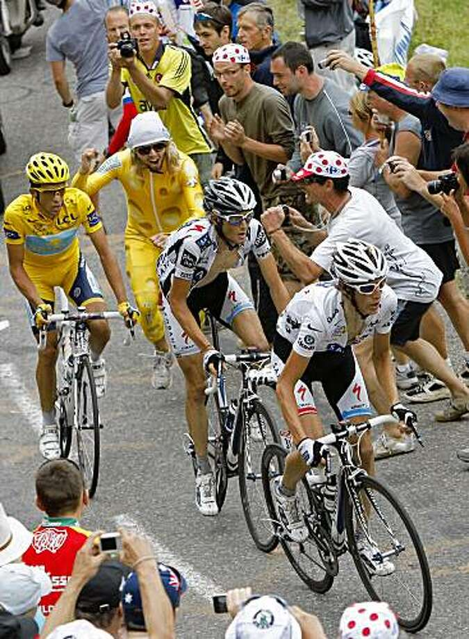 Andy Schleck  of Luxembourg, wearing the best young rider's white jersey, right, stage winner Frank Schleck of Luxembourg, center, and Alberto Contador of Spain, wearing the overall leader's yellow jersey, left, climb Colombiere pass during 17th stage of the Tour de France cycling race over 169.5 kilometers (105.3 miles) with start in Bourg-Saint-Maurice and finish in Le Grand-Bornand, Alps region, France, Wednesday July 22, 2009. Alberto Contador took a second place, and Andy Schleck third place. (AP Photo/Christophe Ena) Photo: Christophe Ena, AP