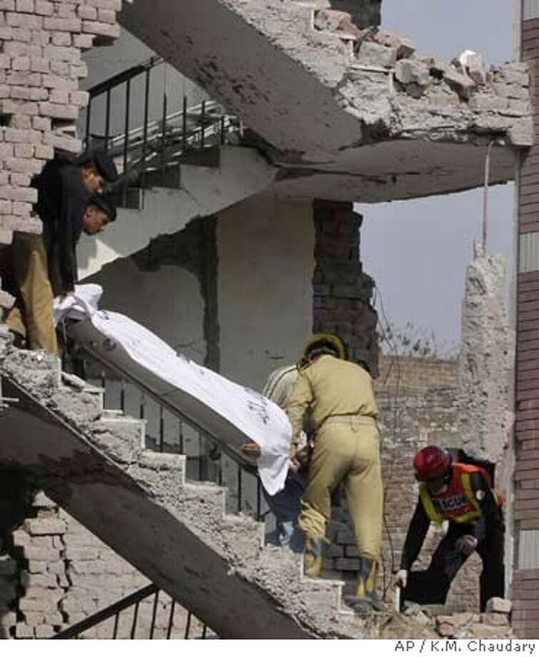###Live Caption:Pakistani rescue workers remove a dead body from the site of a suicide bombing at the office of the Federal Investigation Agency, Tuesday, March 11, 2008, in Lahore, Pakistan. Massive suicide bombs ripped through the seven-story police headquarters and a house in Lahore on Tuesday, killing at least 20 people and wounding more than 150, deepening Pakistan's security crisis as a wave of Islamic militancy sweeps the country. (AP Photo/K.M. Chaudary)###Caption History:Pakistani rescue workers remove a dead body from the site of a suicide bombing at the office of the Federal Investigation Agency, Tuesday, March 11, 2008, in Lahore, Pakistan. Massive suicide bombs ripped through the seven-story police headquarters and a house in Lahore on Tuesday, killing at least 20 people and wounding more than 150, deepening Pakistan's security crisis as a wave of Islamic militancy sweeps the country. (AP Photo/K.M. Chaudary)###Notes:###Special Instructions: Photo: K M Chaudary