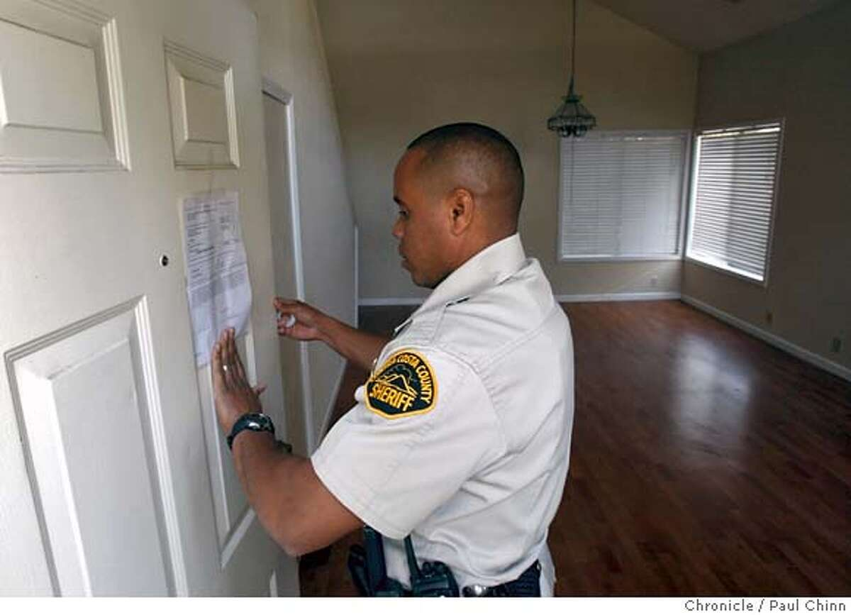 Contra Costa County Sheriff's deputy Doug Odom posts an eviction notice on a home in Antioch, Calif., on Tuesday, Feb. 26, 2008. The tenants had already moved out when the deputies arrived. Photo by Paul Chinn / San Francisco Chronicle Ran on: 03-09-2008 Ellen Anderson takes one last look around before being evicted, above. Deputies Doug Odom (left) and Alex Custodio enter a home to evict people in Antioch, below left. An eviction noticed is left behind in Brentwood, below right. Ran on: 03-08-2008