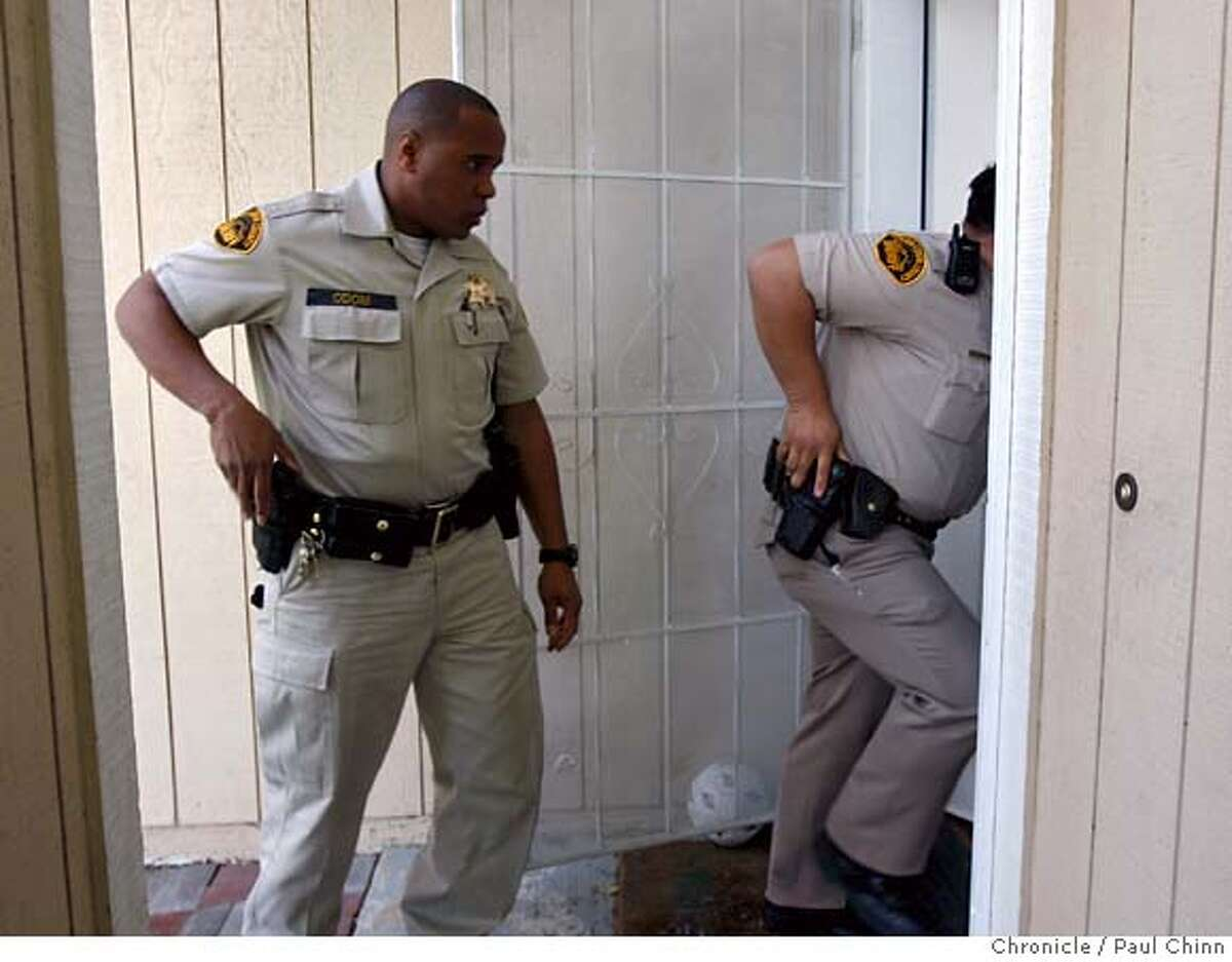 Contra Costa County Sheriff's deputies Doug Odom, left, and Alex Custodio enter a home to evict delinquent tenants in Antioch, Calif., on Tuesday, Feb. 26, 2008. The tenants had already moved out when the deputies arrived. Photo by Paul Chinn / San Francisco Chronicle Ran on: 03-09-2008 Ran on: 03-09-2008 Ellen Anderson takes one last look around before being evicted, above. Deputies Doug Odom (left) and Alex Custodio enter a home to evict people in Antioch, below left. An eviction noticed is left behind in Brentwood, below right.