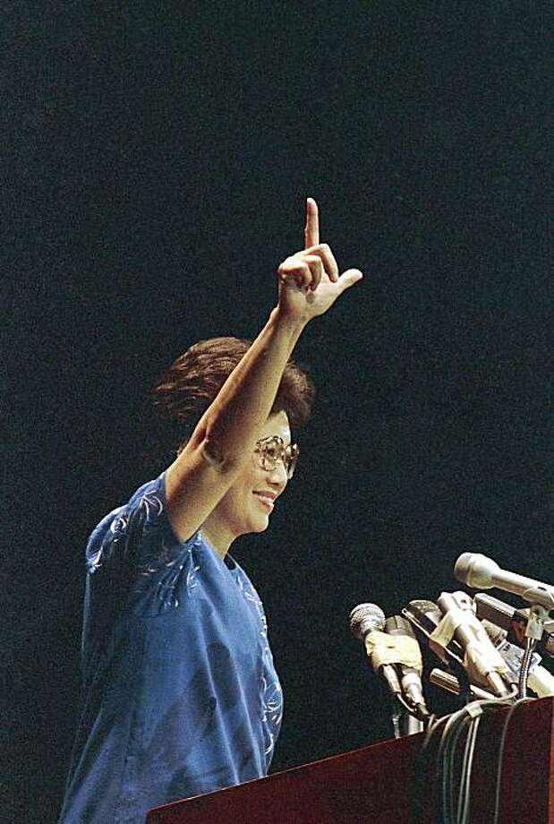 "FILE - in this Nov. 28, 1986 file photo Philippine President Corazon Aquino flashes the ""Laban"" fight sign before addressing a rally to encourage ratification of a draft of a new constitution, Manila, Philippines. Aquino, who swept away a dictator and then sustained democracy by fighting off seven coup attempts in six years, died Friday, July 31, 2009. She was 76. (AP Photo/Alberto Marquez, File) Photo: Alberto Marquez, AP"
