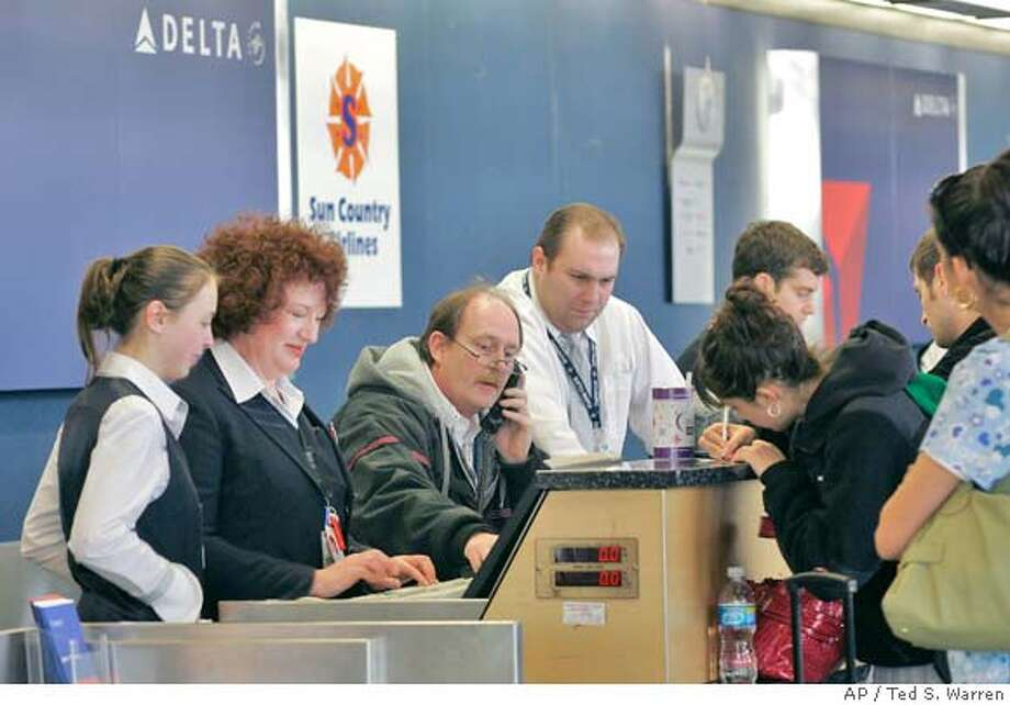 Employees work Tuesday, March 18, 2008 at a Delta Air Lines ticket counter at Seattle-Tacoma International Airport in Seattle. Delta said Tuesday it will offer voluntary severance payouts to roughly 30,000 employees and cut domestic capacity by an extra 5 percent this year as part of an overhaul of its business plan to deal with soaring fuel prices. (AP Photo/Ted S. Warren) Photo: Ted S. Warren