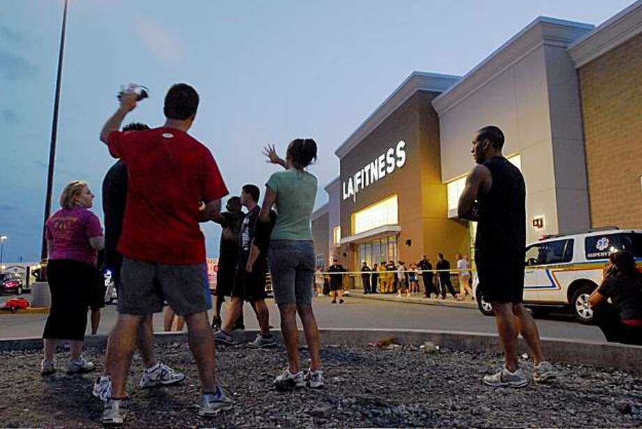 Patrons stand in the parking lot outside of LA Fitness in Bridgeville Pa. after a reported shooting at the health club on Tuesday, Aug. 4, 2009.  (Joe Appel/Tribune-Review) ** MANDATORY CREDIT, PITTSBURGH OUT, HERALD-STANDARD OUT ** Photo: Joel Appel, AP