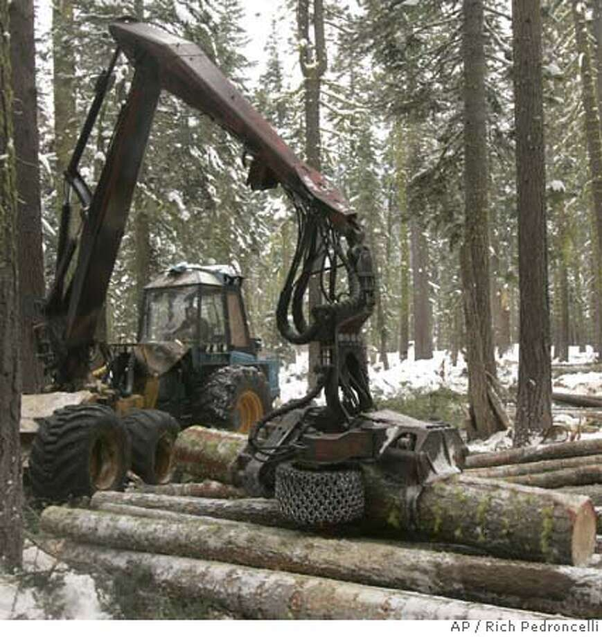 ###Live Caption:Ralph Strang places a tree trimmed of its branches with a cut-to length harvester on a stack of trimmed logs during a forest thinning project near Tahoe City, Calif., Wednesday, Dec. 12, 2007. A bi-state commission is considering a report, Friday, that criticizes years of bureaucratic infighting among agencies with competing agendas, that led to the delay of clearing trees and brush in the Tahoe basin that contributed to the loss of 254 homes in the Angora fire last June.(AP Photo/Rich Pedroncelli)###Caption History:Ralph Strang places a tree trimmed of its branches with a cut-to length harvester on a stack of trimmed logs during a forest thinning project near Tahoe City, Calif., Wednesday, Dec. 12, 2007. A bi-state commission is considering a report, Friday, that criticizes years of bureaucratic infighting among agencies with competing agendas, that led to the delay of clearing trees and brush in the Tahoe basin that contributed to the loss of 254 homes in the Angora fire last June.(AP Photo/Rich Pedroncelli)###Notes:###Special Instructions: Photo: Rich Pedroncelli