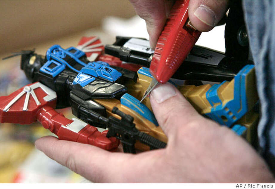 A Customs and Border Protection (CBP) officer scrapes a toy to determine if its painted or molded plastic after the Consumer Product Safety Commission held a news conference Wednesday, March 5, 2008, in Long Beach, Calif., to announce creation of the agency's new Import Surveillance Division. The team, in coordination with CBP, is tasked with inspecting, detecting and stopping hazardous products from entering the United States. (AP Photo/Ric Francis) Photo: Ric Francis