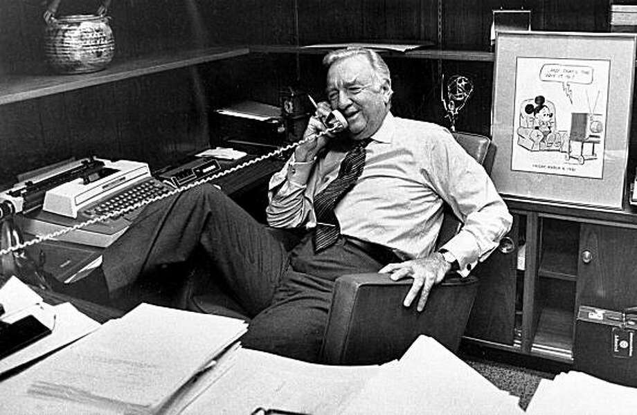In this March 6, 1981 file photo, Walter Cronkite talks on the phone at his office, prior to his final newscast as CBS anchorman in New York City. Behind him is a framed Mickey Mouse cartoon and his Emmy award. Famed CBS News anchor Walter Cronkite, known as the 'most trusted man in America' has died, Friday, July 17, 2009. He was 92. Photo: Associated Press